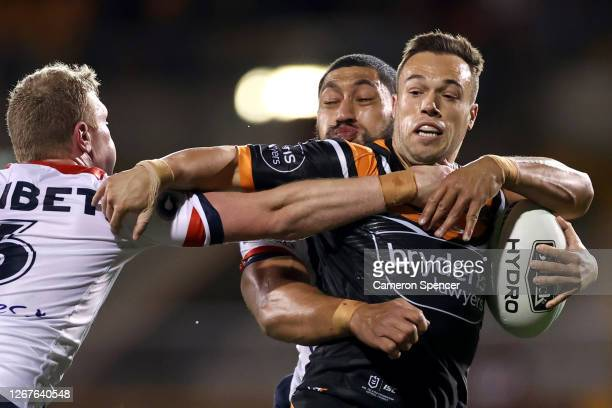 Luke Brooks of the Tigers charges forward during the round 15 NRL match between the Wests Tigers and the Sydney Roosters at Leichhardt Oval on August...