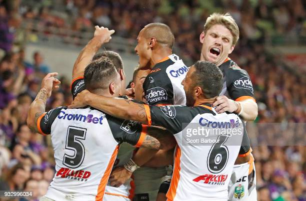 Luke Brooks of the Tigers is congratulated by his teammates after scoring the winning try during the round two NRL match between the Melbourne Storm...