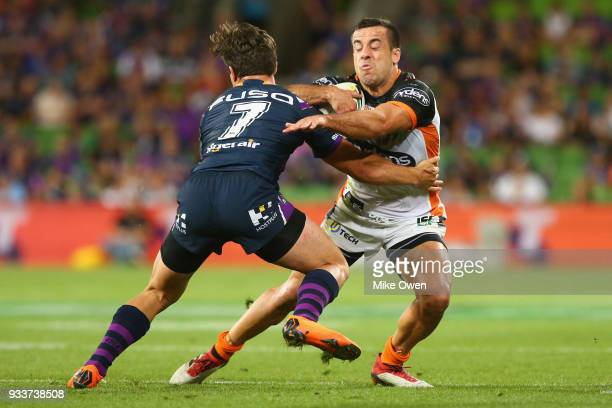 Luke Brooks of the Tigers is tackled by Brodie Croft of the Storm during the round two NRL match between the Melbourne Storm and the Wests Tigers at...