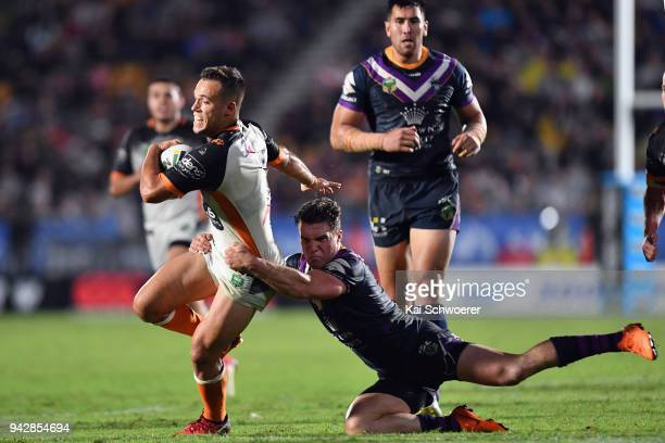 Luke Brooks of the Tigers is tackled by Brodie Croft of the Storm during the round five NRL match between the Wests Tigers and the Melbourne Storm at...