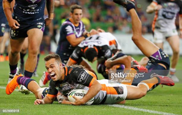 Luke Brooks of the Tigers scores the winning try as Billy Slater of the Melbourne Storm looks on behind during the round two NRL match between the...