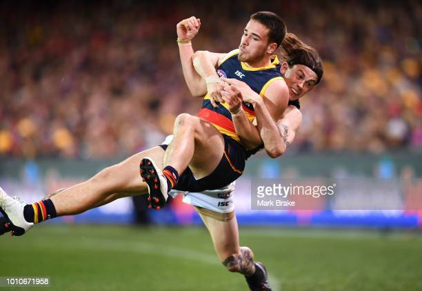 Luke Brown of the Adelaide Crows tackled over the boundary by Jasper Pittard of Port Adelaide during the round 20 AFL match between the Adelaide...