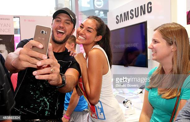 Luke Bryan takes a selfie with fans using the new Galaxy S6 edge at the TMobile Times Square store in New York to celebrate the unveiling of...