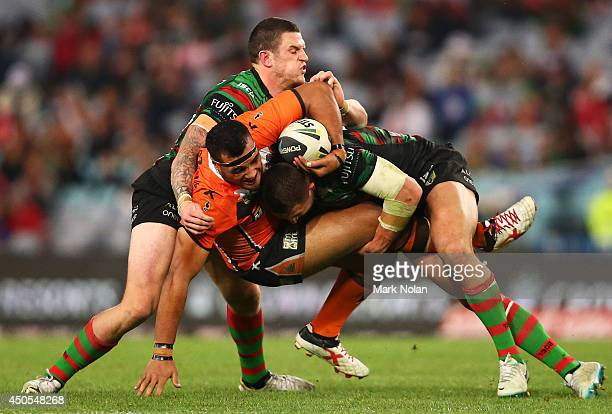 Luke Burgess and Sam Burgess of the Rabbitohs tackle Ava Seumanufagai of the Tigers during the round 14 NRL match between the South Sydney Rabbitohs...