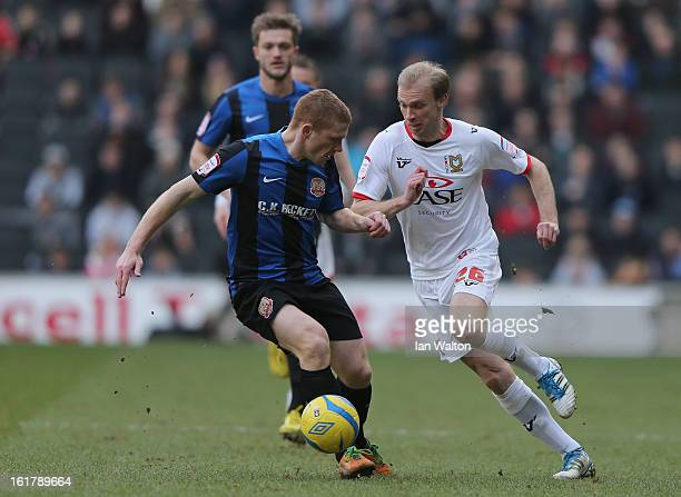 Luke Chadwick of MK Dons is challenged by Bobby Hassell of Barnsley during the FA Cup Fifth Round match between MK Dons and Barnsley at StadiumMK on...