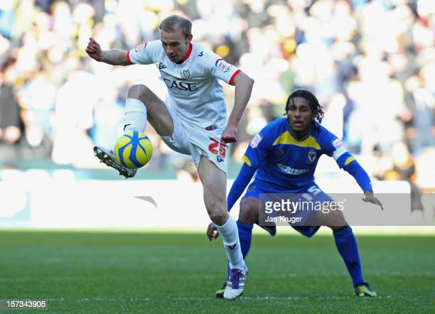 Luke Chadwick of MK Dons is watched by Jim Fenlon of AFC Wimbledon during the FA Cup with Budweiser Second Round match between MK Dons and AFC...