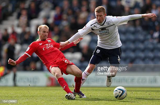 Luke Chadwick of MK Dons passes the ball away from Chris Robertson of Preston North End during the npower League One match between Preston North End...