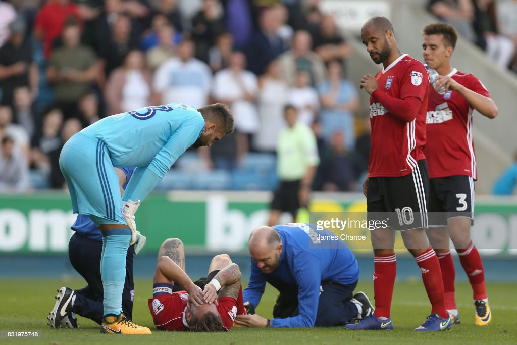 Luke Chambers of Ipswich receives treatment from the medical team as his team mates Bartosz Bialkowski of Ipswich (L) and David McGoldrick of Ipswich (R) check to see if he is okay during the Sky Bet Championship match between Millwall and Ipswich Town at The Den on August 15, 2017 in London, England.