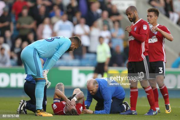 Luke Chambers of Ipswich receives treatment from the medical team as his team mates Bartosz Bialkowski of Ipswich and David McGoldrick of Ipswich...