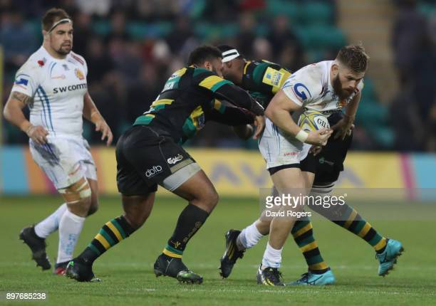 Luke CowanDickie of Exeter is tackled by Jamal FordRobinson and Courtney Lawes during the Aviva Premiership match between Northampton Saints and...