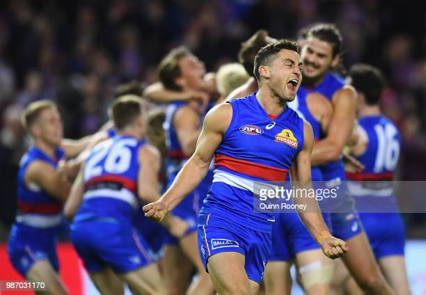 Luke Dahlhaus and his Bulldogs team mates celebrate winning the round 15 AFL match between the Western Bulldogs and the Geelong Cats at Etihad...