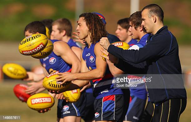 Luke Dahlhaus and Tory Dickson of the Bulldogs pass the ball during a Western Bulldogs AFL training session at Whitten Oval on July 31 2012 in...