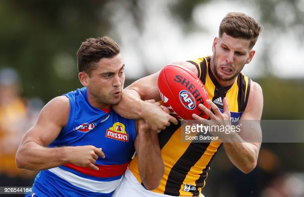 Luke Dahlhaus of the Bulldogs and Luke Breust of the Hawks compete for the ball during the AFL JLT Community Series match between the Western...