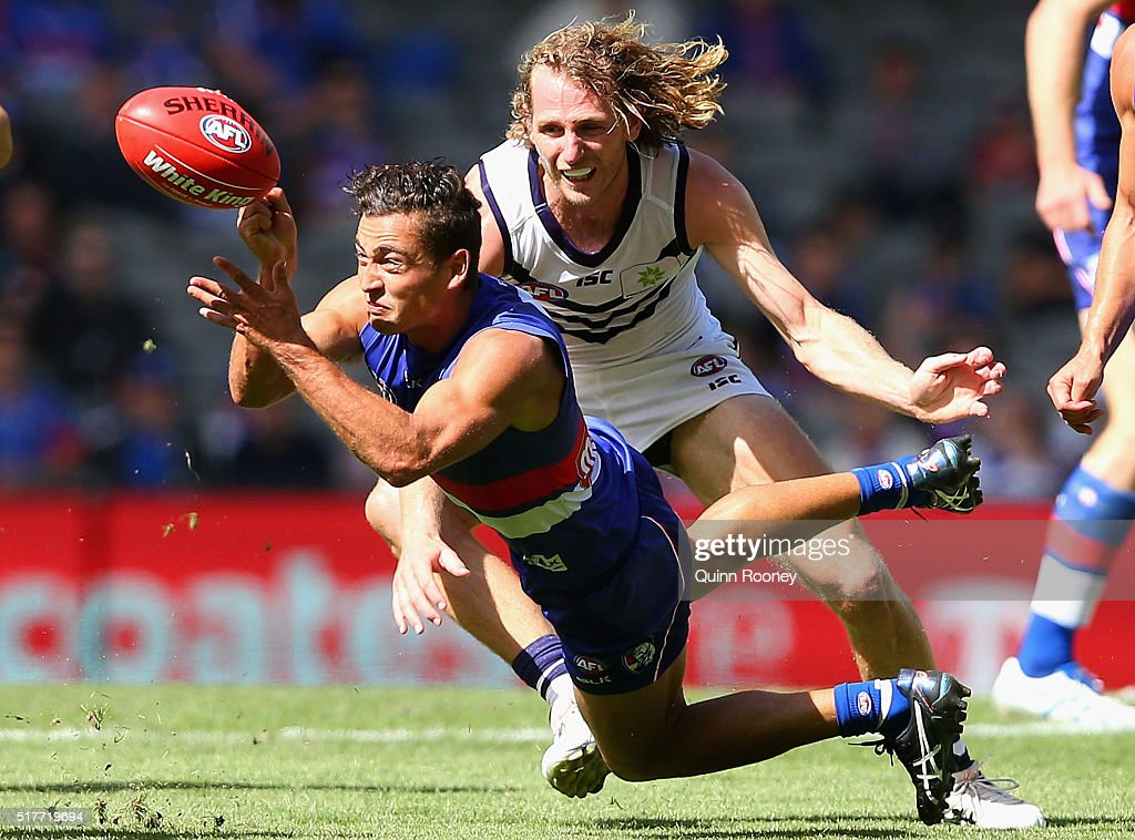 Luke Dahlhaus of the Bulldogs handballs whilst being tackled by David Mundy of the Dockers during the round one AFL match between the Western Bulldogs and the Fremantle Dockers at Etihad Stadium on March 27, 2016 in Melbourne, Australia.