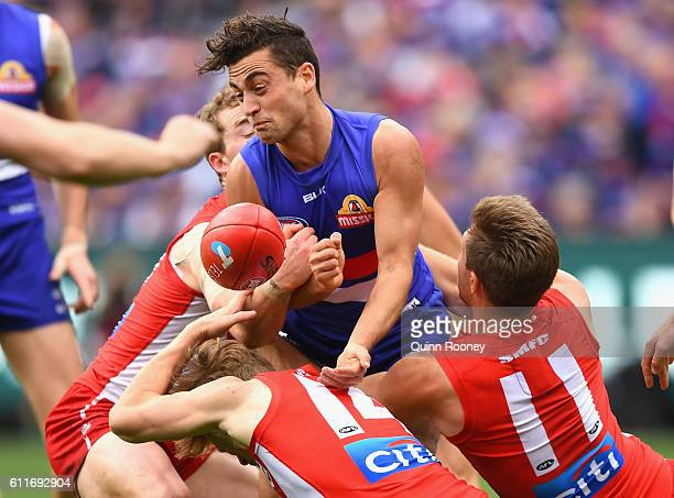 Luke Dahlhaus of the Bulldogs handballs whilst being tackled during the 2016 AFL Grand Final match between the Sydney Swans and the Western Bulldogs...