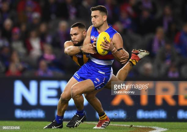 Luke Dahlhaus of the Bulldogs is tackled by Jarman Impey of the Hawks during the round 16 AFL match between the Western Bulldogs and the Hawthorn...