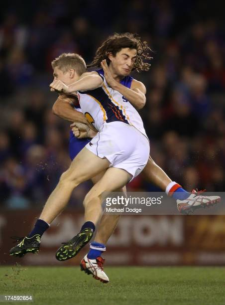 Luke Dahlhaus of the Bulldogs kicks the ball as Scott Sellwood of the Eagles bumps him during the round 18 AFL match between the Western Bulldogs and...