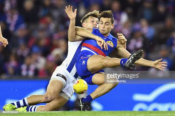 Luke Dahlhaus of the Bulldogs kicks whilst being tackled by Shaun Higgins of the Kangaroos during the round 14 AFL match between the Western Bulldogs...