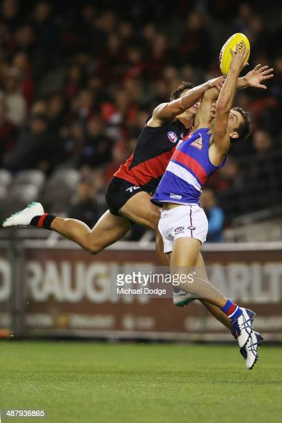Luke Dahlhaus of the Bulldogs marks the ball against Mark Baguley of the Bombers during the round seven AFL match between the Essendon Bombers and...