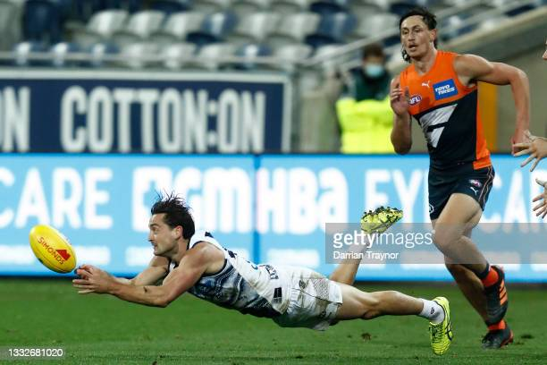 Luke Dahlhaus of the Cats handballs during the round 21 AFL match between Geelong Cats and Greater Western Sydney Giants at GMHBA Stadium on August...
