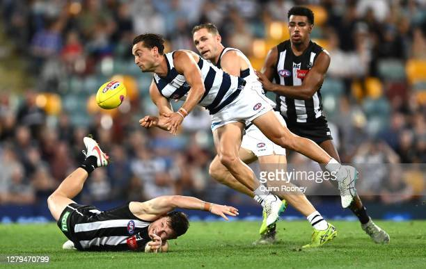Luke Dahlhaus of the Cats handballs over Taylor Adams of the Magpies during the AFL First Semi Final match between the Geelong Cats and the...