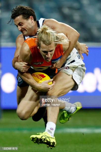 Luke Dahlhaus of the Cats tackles Nick Haynes of the Giants during the round 21 AFL match between Geelong Cats and Greater Western Sydney Giants at...