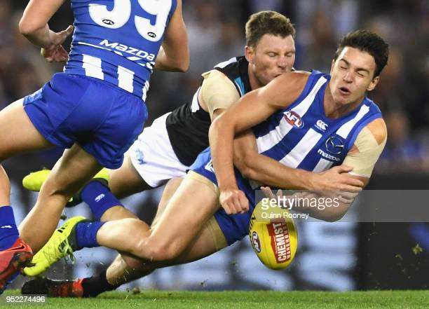 Luke DaviesUniacke of the Kangaroos handballs whilst being tackled by Brad Ebert of the Power during the round six AFL match between the North...