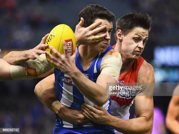 Luke DaviesUniacke of the Kangaroos is tackled by Callum Sinclair of the Swans during the round 17 AFL match between the North Melbourne Kangaroos...