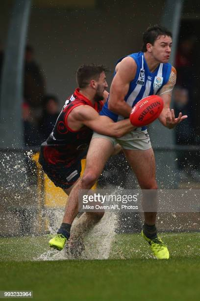 Luke DaviesUniacke of the Kangaroos is tackled by James Munro of the Demons during the round 14 VFL match between Casey and North Melbourne at Casey...