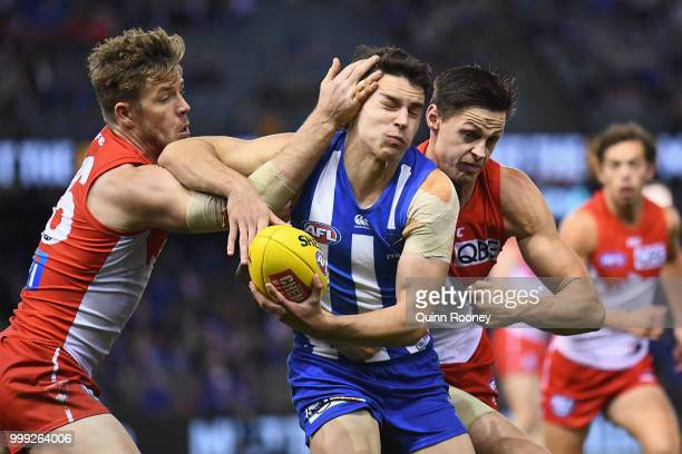 Luke DaviesUniacke of the Kangaroos is tackled by Luke Parker and Callum Sinclair of the Swans during the round 17 AFL match between the North...