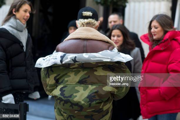 Luke Day wears a red Vetements x Canada Goose camouflage down parka over a brown shearling jacket and a black cap outside the Balenciaga show at...