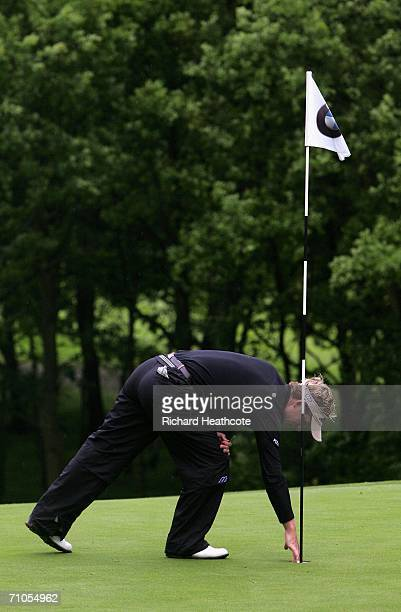 Luke Donald of England collects his ball as he hits a hole in one on the 2nd hole during the Second Round of the BMW Championship at The Wentworth...