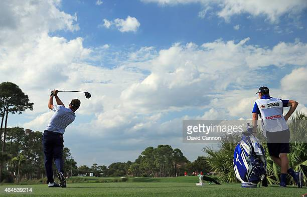 Luke Donald of England drives from the second tee watched by his caddie John McLaren during the first round of The Honda Classic on the Champions...