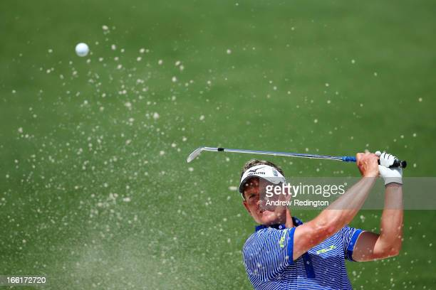 Luke Donald of England hits a shot from a bunker during a practice round prior to the start of the 2013 Masters Tournament at Augusta National Golf...