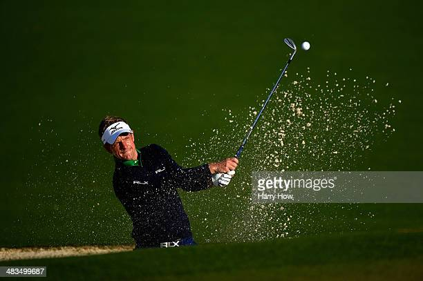 Luke Donald of England hits a shot from a greenside bunker during a practice round prior to the start of the 2014 Masters Tournament at Augusta...