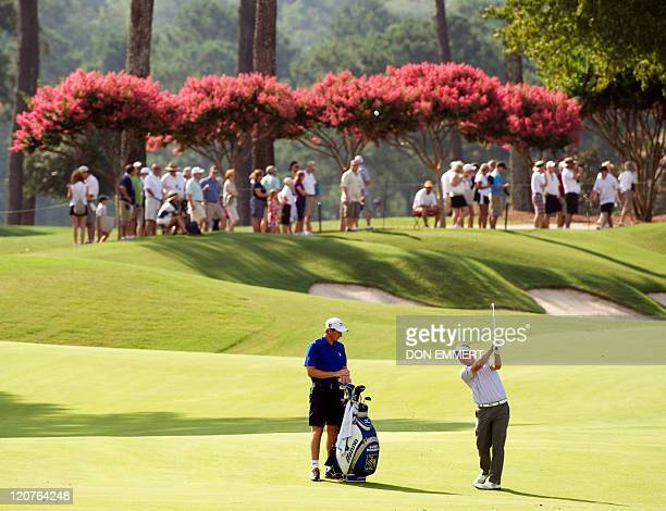 Luke Donald of England hits his approach shot to the 18th green during a practice round of the 2011 PGA Championship Tournament at Atlanta Athletic...