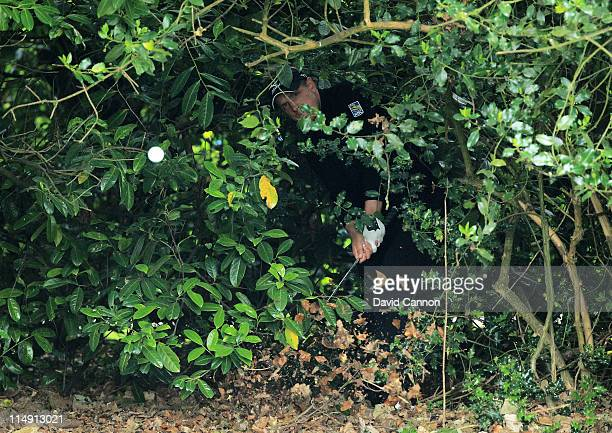 Luke Donald of England hits his second shot from the bushes on the 18th hole during the third round of the BMW PGA Championship at the Wentworth Club...