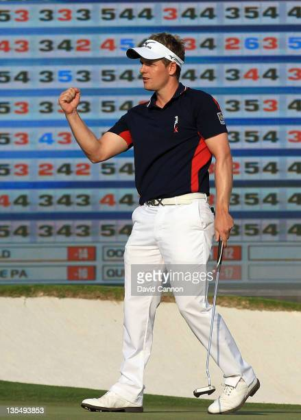 Luke Donald of England holes a birdie putt at the par 3, 17th hole during the final round of the Dubai World Championship on the Earth Course at the...