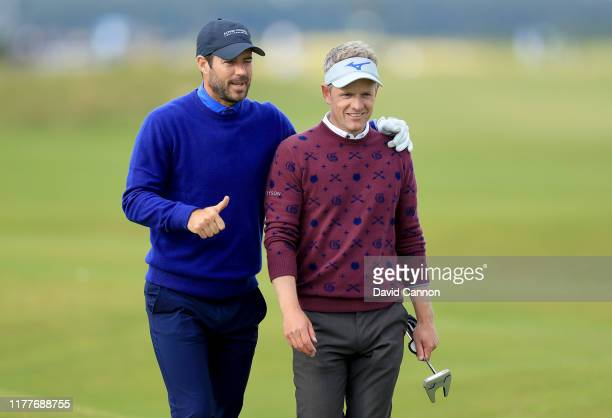 Luke Donald of England is congratulated by his playing partner Jamie Redknapp after playing his second shot on the 17th hole during the third round...