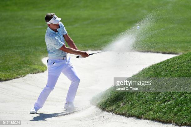 Luke Donald of England plays a shot from a greenside bunker on the ninth hole during the first round of the 2018 RBC Heritage at Harbour Town Golf...