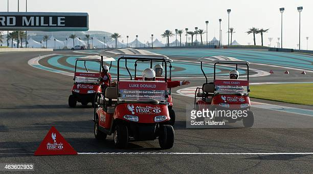 Luke Donald of England races a golf cart with Sergio Garcia Matteo Manassero and Paul Casey at the Yas Marina Circuit Abu Dhabi before the start of...
