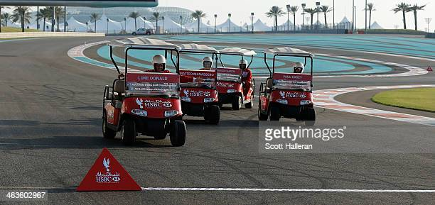 Luke Donald of England races a golf cart with Sergio Garcia, Matteo Manassero and Paul Casey at the Yas Marina Circuit Abu Dhabi before the start of...