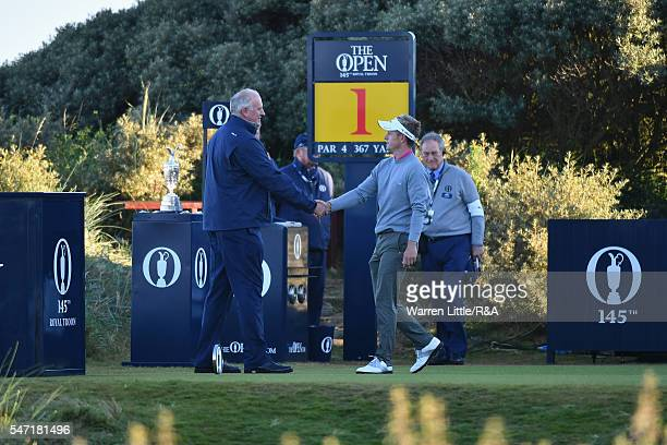 Luke Donald of England shakes hands with starter David Lancaster on the 1st tee during the first round on day one of the 145th Open Championship at...