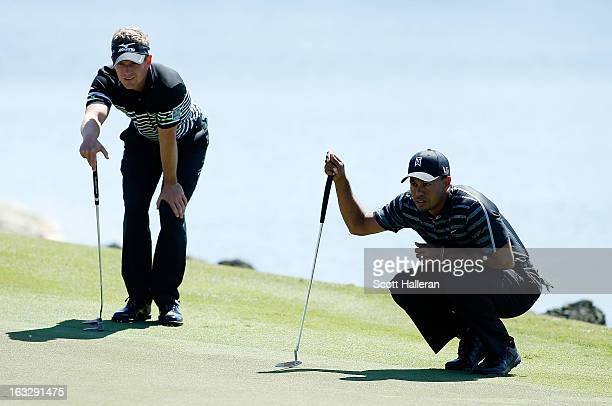 Luke Donald of England waits with Tiger Woods on the tenth green during the first round of the WGCCadillac Championship at the Trump Doral Golf...