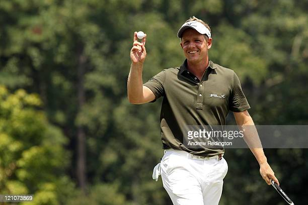 Luke Donald waves to the gallery after a birdie on the 14th hole during the third round of the 93rd PGA Championship at the Atlanta Athletic Club on...