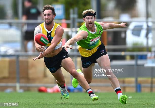 Luke Dunstan of the Saints handballs whilst being tackled during a St Kilda Saints AFL training session at Maroochydore Multi Sport Complex on...
