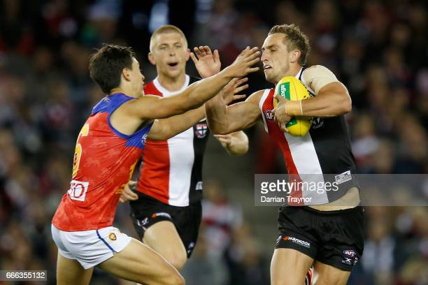 Luke Dunstan of the Saints shrugs the tackle of Hugh McCluggage of the Lions during the round three AFL match between the St Kilda Saints and the...