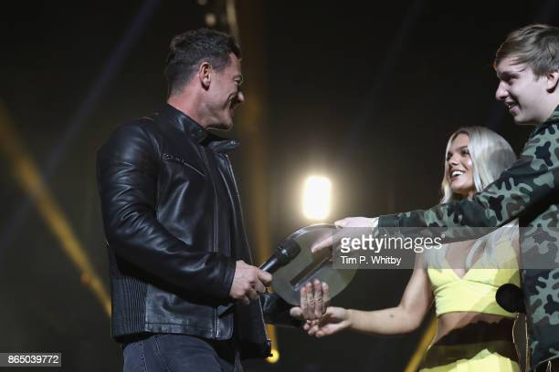 Luke Evans is presented with the award for Best Film for 'Beauty and the Beast' by Louisa Johnson and George Ezra on stage during the BBC Radio 1...
