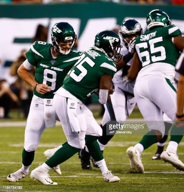 Luke Falk hands off the ball to Elijah McGuire of the New York Jets during the preseason game against the Philadelphia Eagles at MetLife Stadium on...