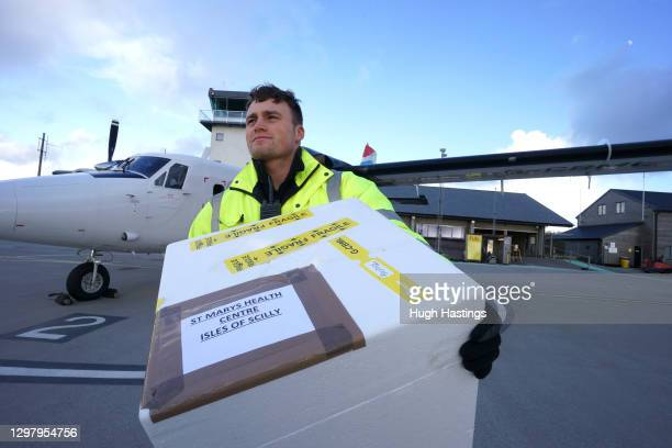 Luke Flack, ground crew at Land's End Airport, with the first box of Covid-19 vaccines to be supplied to the Isles of Scilly via Skybus at Land's End...